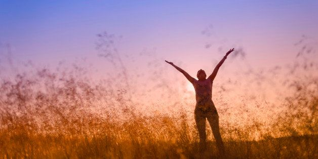 silhouette of a woman lifting her hands in worship, in a meadow at sunset.
