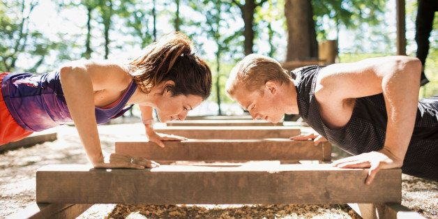 Side view of couple doing push-ups at outdoor gym