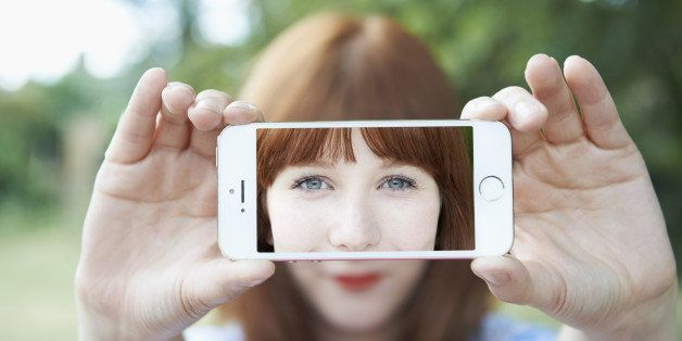 woman holding up mobile with selfie