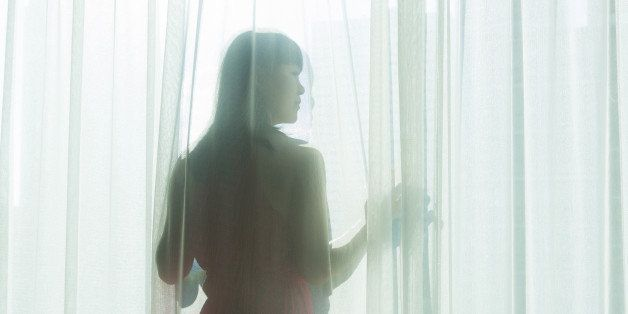 a woman in a red dress looking out of a sunlit window