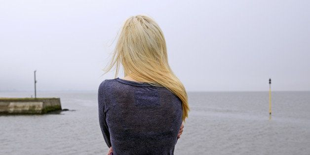 Woman looking out from misty quayside