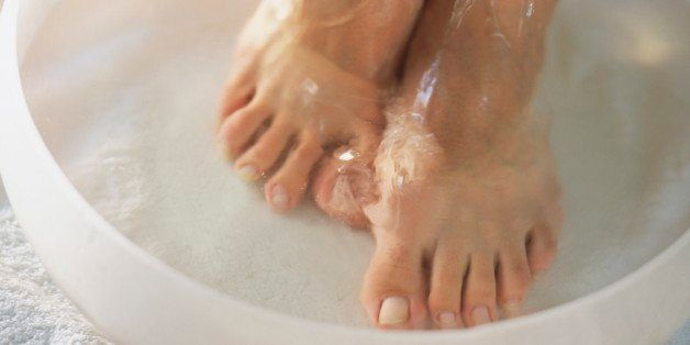 Woman's bare feet in shallow bowl of water on white towel, one hand spreading water on feet, close-up.