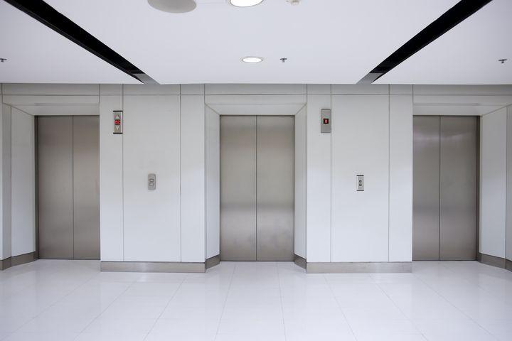 three elevator doors in office...