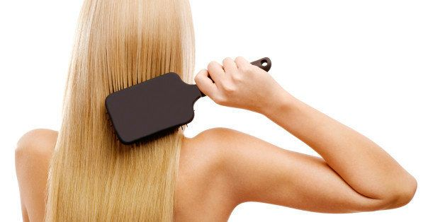 Young blonde lady is combing her beautiful long hair