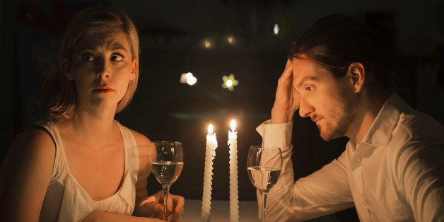 A couple appear to be in a state of tension as if grappling with a serious problem. They are drinking white wine and sit at a table lit by candlelight.
