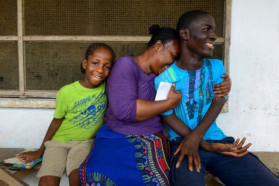 On 14 November, (centre) Martu Weefor embraces Harris Wreh, 17, in the Paynesville suburb of Monrovia, the capital. Next to h
