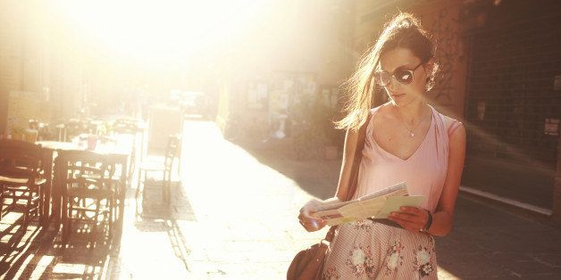 young brunette sightseeing on the street, looking at the map, lit by the magic hour sunlight.