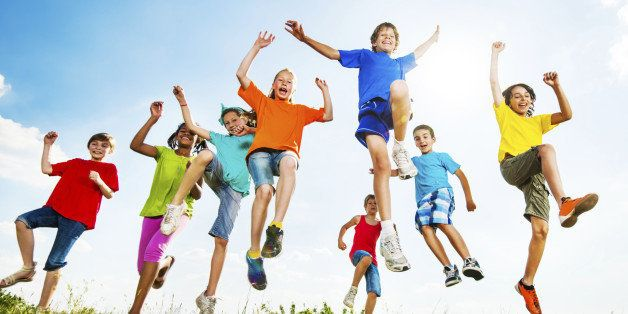 Happy children jumping with raised arms and enjoying in a beautiful nature.