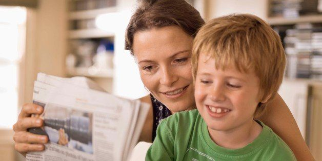 Mother and son reading newspaper together