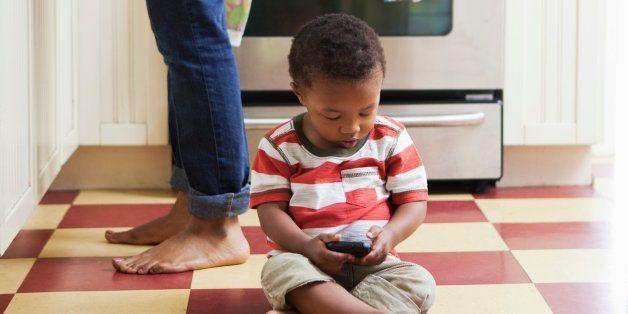 Baby boy sitting on kitchen floor playing