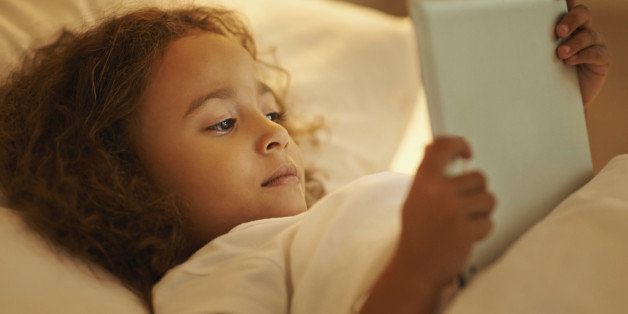 A young girl lying on her bed while using a digital tablet