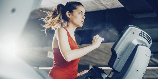 Healthy young woman in GYM running on treadmill