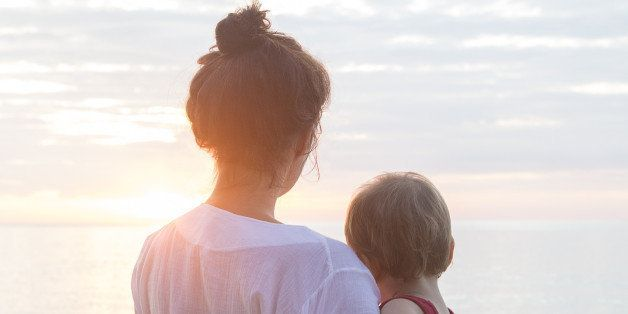 mother and baby son looking at sunrise at the beach in thailand