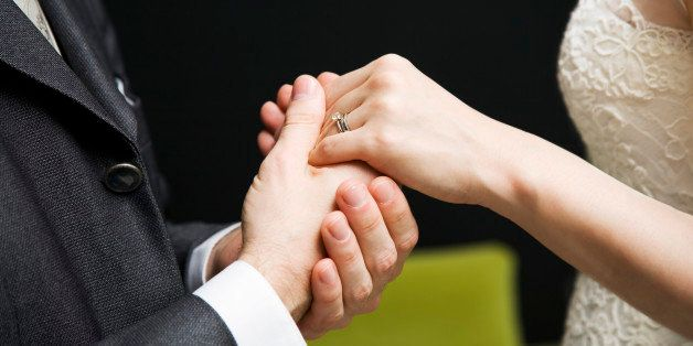 Bride and groom with wedding rings, holding hands, mid section, side view
