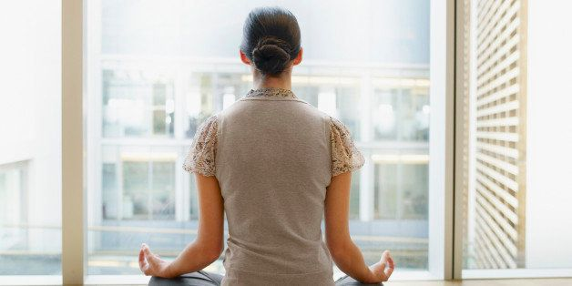 Businesswoman doing yoga in modern office