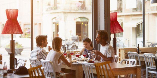 Multi-ethnic friends having lunch in restaurant