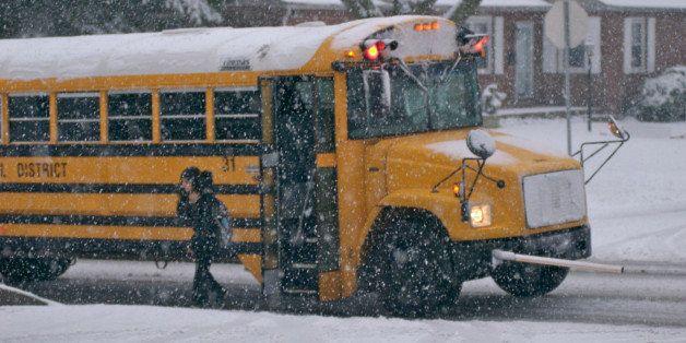 Girl (10-11) disembarking school bus in snow