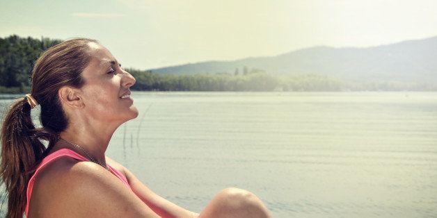 woman meditating on the bank of a lake