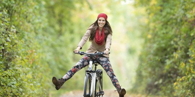 Beautiful woman with a perfect natural expression riding her bicycle through an autumn forest. Nikon D800e.