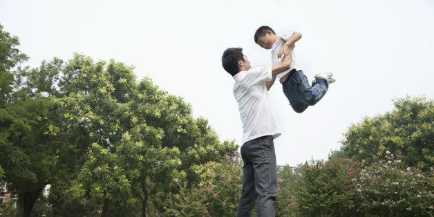 Chinese father and son playing in park