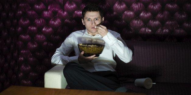 Man watching fascinating program in TV and eating popcorn
