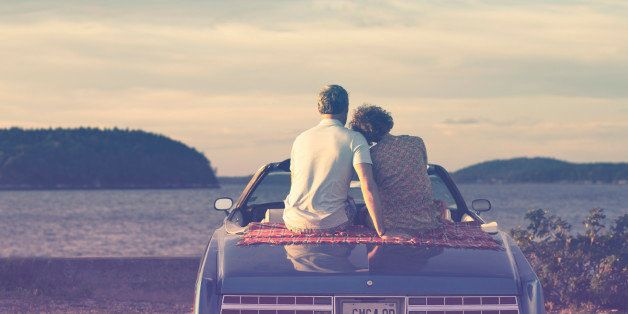 Couple sitting in convertible and embracing at sunset