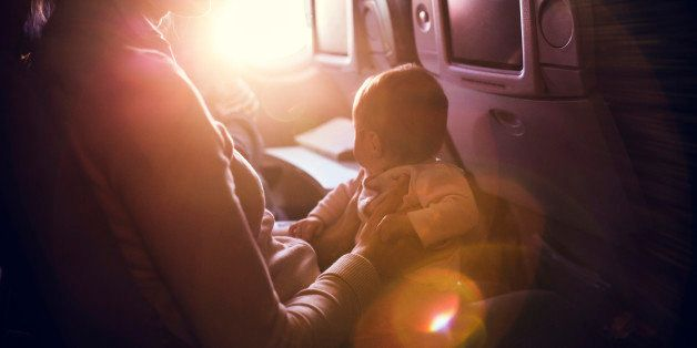 A mother and her baby girl sit in a passenger airline seat, the sun shining brightly in through the plane window.  While air travel with children can be difficult, both mom and child are content, the mother with a smile on her face. Horizontal image.  INTENTIONAL LENS FLARE.
