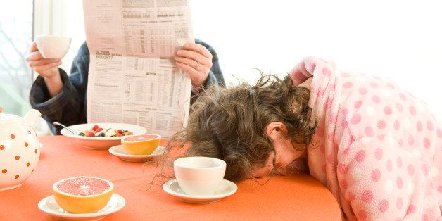 Tired woman with her husband falling asleep during breakfast