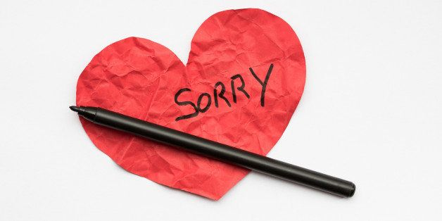 Crumpled red paper heart with pen and the word Sorry written on it.
