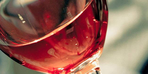 Close-up of a man's hand holding a glass of red wine
