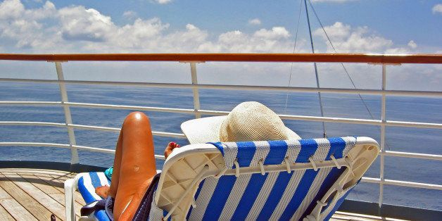 A woman sits on a lounge chair and overlooks the ocean from a cruise ship