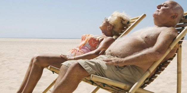 Senior couple sitting in chairs on beach, eyes closed