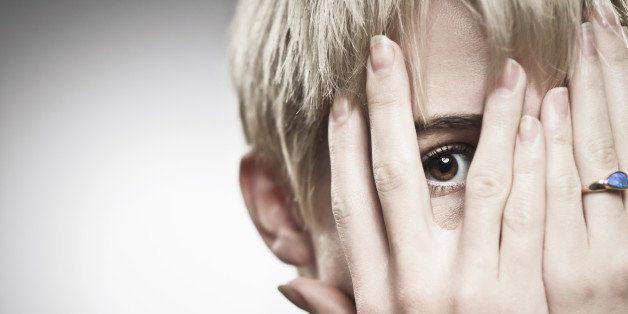 Fearful girl peeking through her fingers.