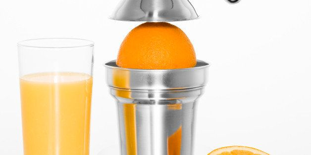 Cut out of a citrus juicer with a glass of orange juice and oranges on a white background