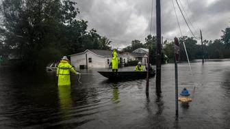 Workers with Duke Energy move through Lumberton, North Carolina by boat in attempts to restore power to customers on Sunday after intense flooding in the town.