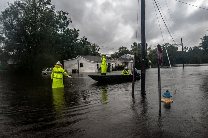 Workers with Duke Energy move through Lumberton, North Carolina, by boat in attempts to restore power to customers on Sunday