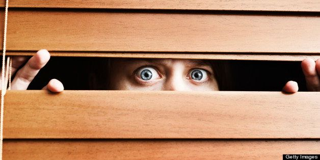 A  frightened young woman  stares, wide eyed, through the slats of a wooden venetian blind. She could be having home security
