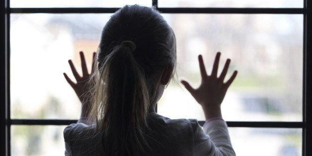 Young girl at window (in partial silhouette) hands pressed against window, pensive or wanting out?