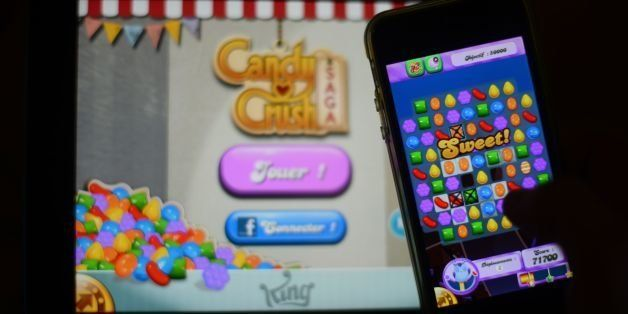 (FILES) In this file picture taken on January 25, 2014 a man plays at Candy Crush Saga on his Iphone in Rome. Candy Crush is one of the top online games developped by King.com.   With three young children and a full-time job, Emma Martini has little time for computer games. But every night she sits quietly at the end of her son's bed to reassure him while he falls asleep -- and plays Candy Crush. AFP PHOTO / GABRIEL BOUYS        (Photo credit should read GABRIEL BOUYS/AFP/Getty Images)