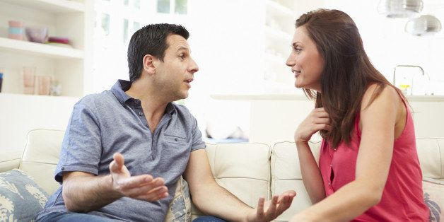 Hispanic Couple Sitting On Sofa Arguing During The Day