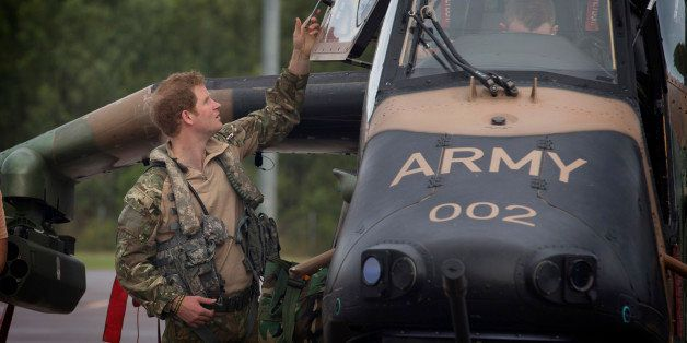 In this April 14, 2015, photo provided by the Australian Defence on Monday, April 20, 2015, Britain's Prince Harry opens the door of an Armed Reconnaissance Helicopter (ARH) Tiger from 1st Aviation Regiment prior to a familiarization flight at Robertson Barracks in Darwin, Australia. Capt. Wales was briefed on Australian Army's North-West Mobile Force's operations and received his orders before he headed out on a patrol. (Cpl. Oliver Carter/Australian Defence via AP)