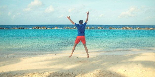 Happy young man jumping in the air at sea on white snd beach