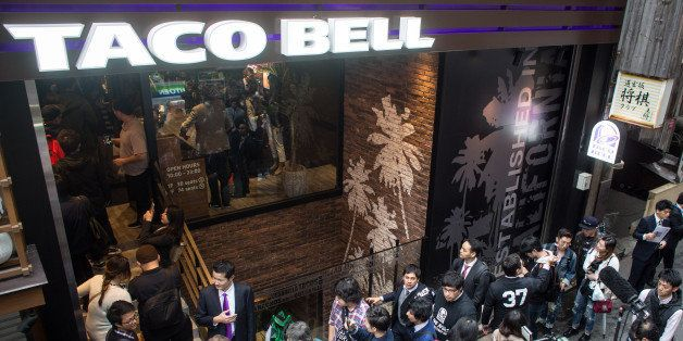TOKYO, JAPAN - APRIL 21: People wait outside the new Taco Bell store ahead of it's official opening on April 21, 2015 in Tokyo, Japan. The new store operated by Asrapport Dining Co. is the first store to be opened in Japan in 20 years. The Mexican-themed fast food chain entered the Japanese market in the 1980's but pulled out due to poor sales, operating stores only on restricted U.S military bases.  (Photo by Chris McGrath/Getty Images)