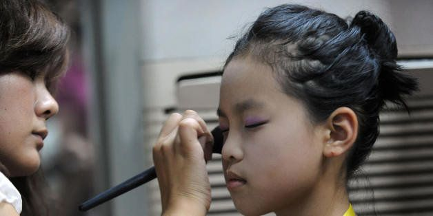 A Chinese mother helps prepare her daughter for a children's beauty and modeling contest in Hefei, in eastern China's Anhui province on July 27, 2009.  Beauty pageants were once considered reviled displays of western decadence but have become big business in Communist-ruled China following more than two decades of economic reforms.  CHINA OUT  AFP PHOTO (Photo credit should read AFP/AFP/Getty Images)