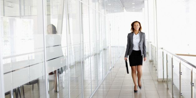 Businesswoman walking along the office corridor
