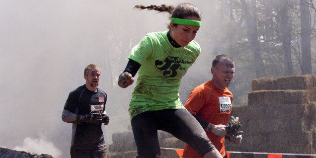 POCONO MANOR, PA - APR 28: A woman runs through the Fire Walker obstacle at Tough Mudder on April 28, 2012 in Pocono Manor, Pennsylvania. The course is designed by British Royal troops.