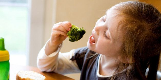 A 4 year old girl sitting at the table enjoying a healthy lunch. She is eating broccoli with her hands, her mouth is wide open. Soft window lighting.