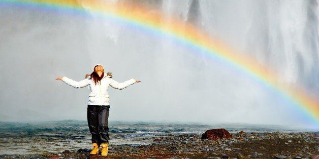 Happiness, my friend lying under the rainbow at Skogafoss waterfalls in Iceland