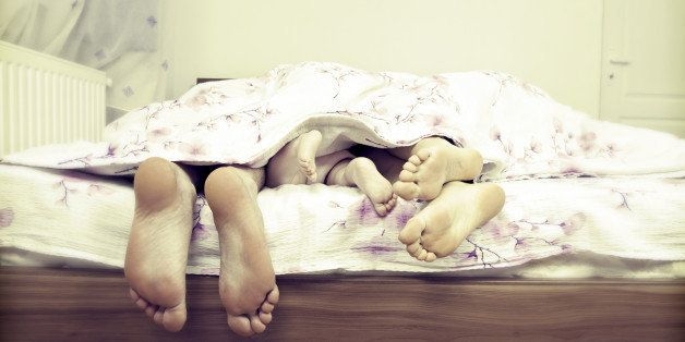 Tree pairs of legs - the happy family in bed:  father, mother and baby