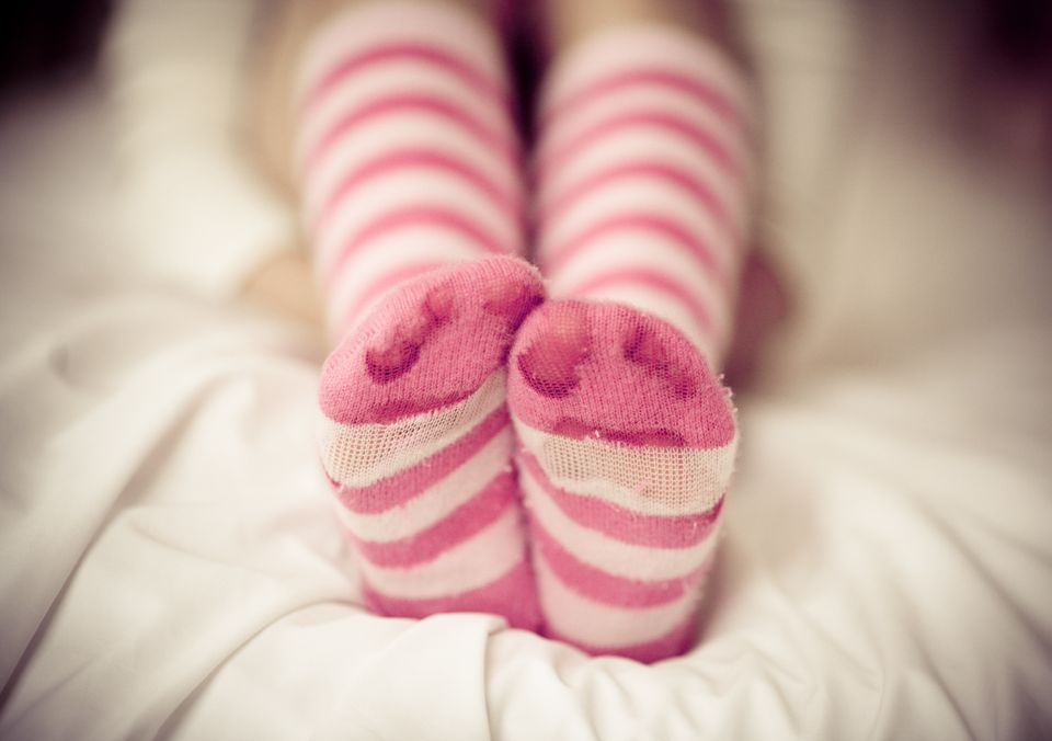 Human legs in pink and white striped socks on bed.If your feet are dry, cracked, or calloused, there's a simple trick that wi